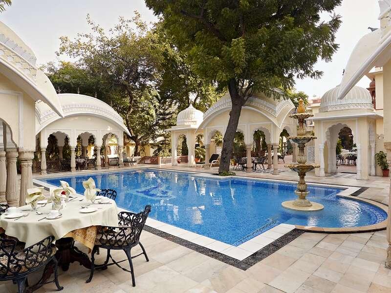 Ein schöner, gepflegter Swimmingpool, umgeben von klassischen Bogenkuppeln und Chattris: Das Hotel Alsisar Haveli, das einer Maharadschafamilie gehört, ist unser Quartier für zwei Nächte in Jaipur auf unserer Rundreise in Rajasthan.