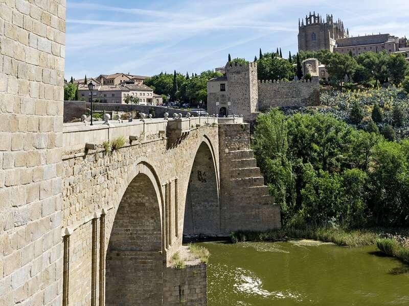 Die alte Steinbogenbrücke Puente de San Martín in Toledo überspannt den Fluss Tajo. Ein bildschönes Panorama auf Ihrer Rundreise durch Kastilien.