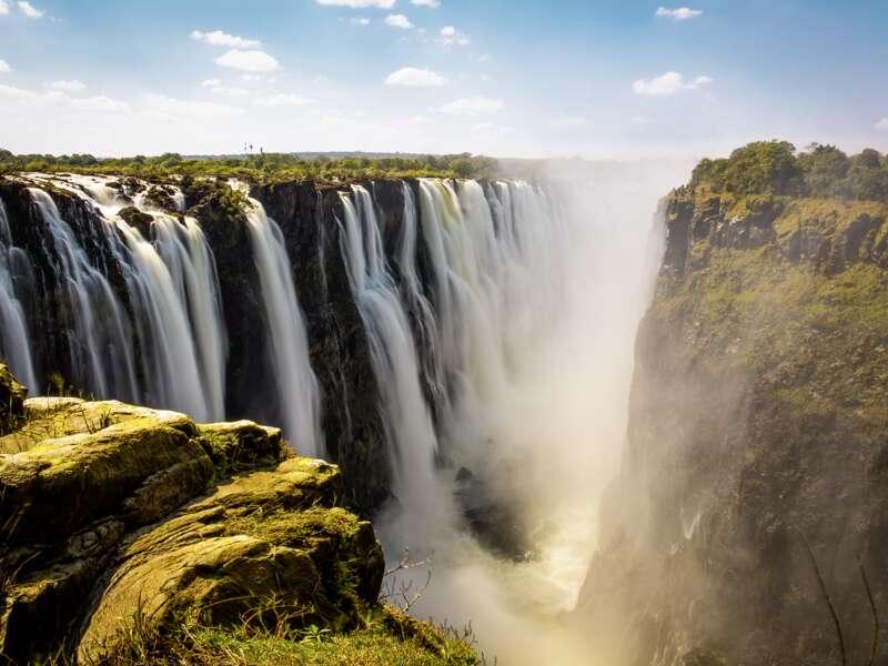 Von unserer Rundreise durch Namibia machen wir einen Abstecher zu den Viktoriafällen, breiter Wasserfall und majestätische Naturgewalt des Sambesis an der Grenze zwischen Sambia und Simbabwe. Seit 1989 gehören sie zum UNECSO-Weltnaturerbe.