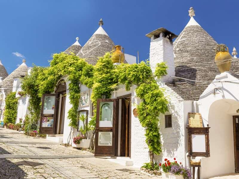Durch Oliven- und Mandelhaine geht es auf unserer me&more Reise durch Apulien nach Alberobello, die Hauptstadt der Trullis. Wie Schlümpfe, die unter Zipfelmützen aus Kalksteinen hervorlugen, stehen die weiß getünchten Rundbauten in der Landschaft.