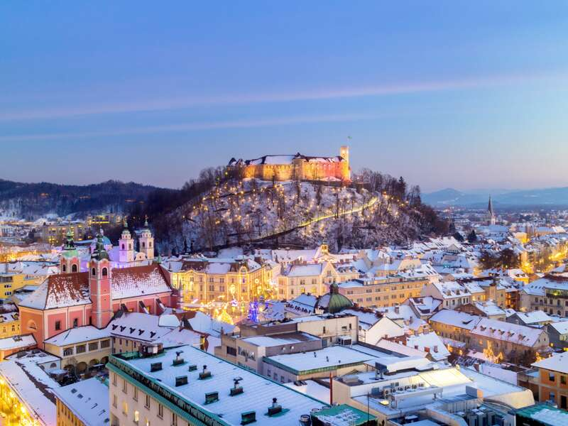 Die Dächer der Altstadt von Ljubljana sind verschneit - darüber thront die Burg.