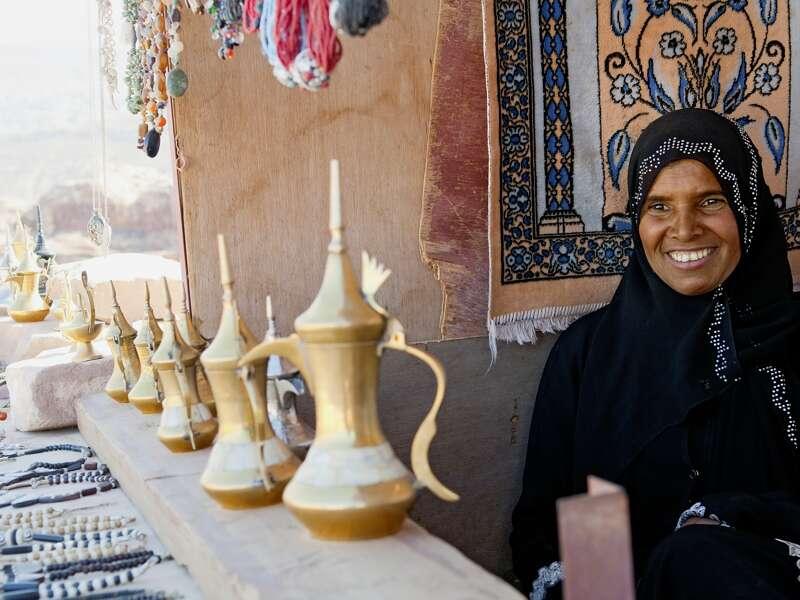 Eine  traditionell gekleidete Frau sitzt an einem Marktstand in Petra und bietet messingfarbene Kaffeekannen und Schmuck zum Verkauf an.