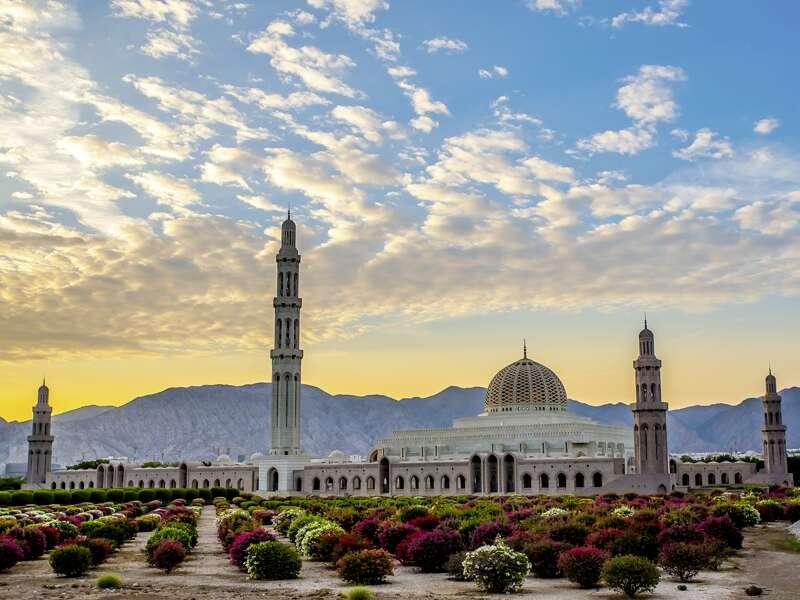 Wir sehen die Sultan-Qaboos-Moschee in Maskat vor bergigem Hintergrund bei Sonnenuntergang.