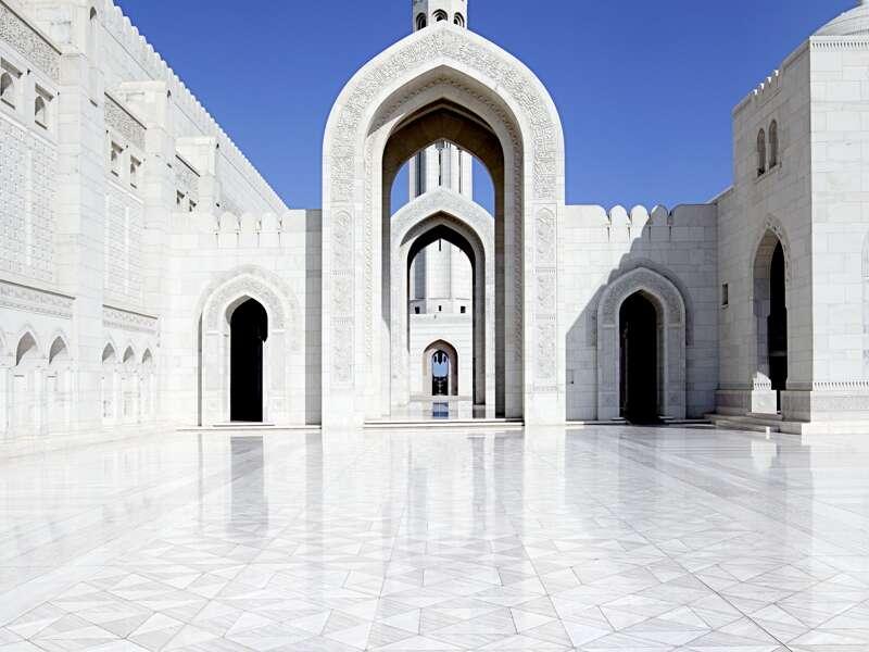 Blick auf einen der Innenhöfe der Sultan Qaboos-Moschee in Maskat mi tweiß- glänzendem Marmorboden. Durch einen spitzen Torbogen erblickt man einen Teil des Minaretts.