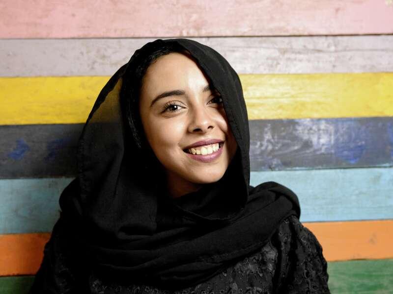 Junge Frau aus dem Oman mit schwarzem Kopftuch vor bunter Wand
