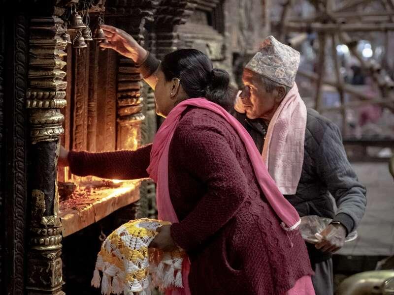Auf unserer Studienreise Nepal - am Thron der Götter begegnen wir überall der lebendigen Spiritualität der Nepalesen. Hier entzünden Gläubige in der Gebetsnische eines Tempels Butterlampen und bitten die Götter um ihren Segen.