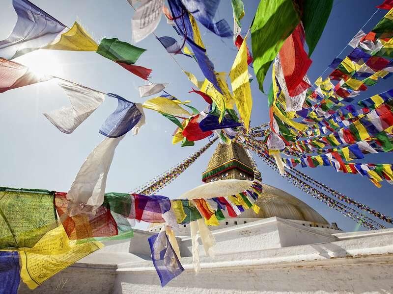 Gebetsfahnen weisen den Weg: Auf unserer Studienreise Nepal - am Thron der Götter besuchen wir den schneeweißen Stupa von Bodnath. Er ist die bedeutendste Kultstätte des Tibetischen Buddhismus im Kathmandutal (UNESCO-Welterbe).