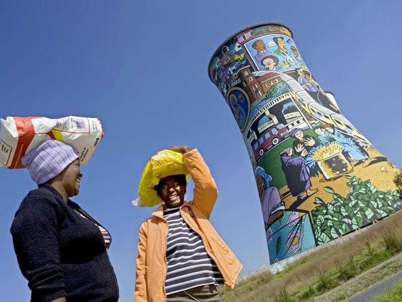 Bunte Eindrücke gibt es auf unserer Preiswert-Studienreise Südafrika - Höhepunkte sehr viele. Doch nicht nur die Natur ist farbenfreudig, sondern auch die Menschen - und sogar dieser bemalte ehemalige Kühlturm in der Township Soweto.