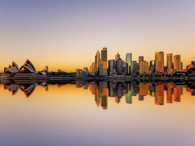 Bei unserer Studienreise Australien - Höhepunkte des Kontinents erleben Sie die Skyline und das Opernhaus von Sydney im Abendlicht.