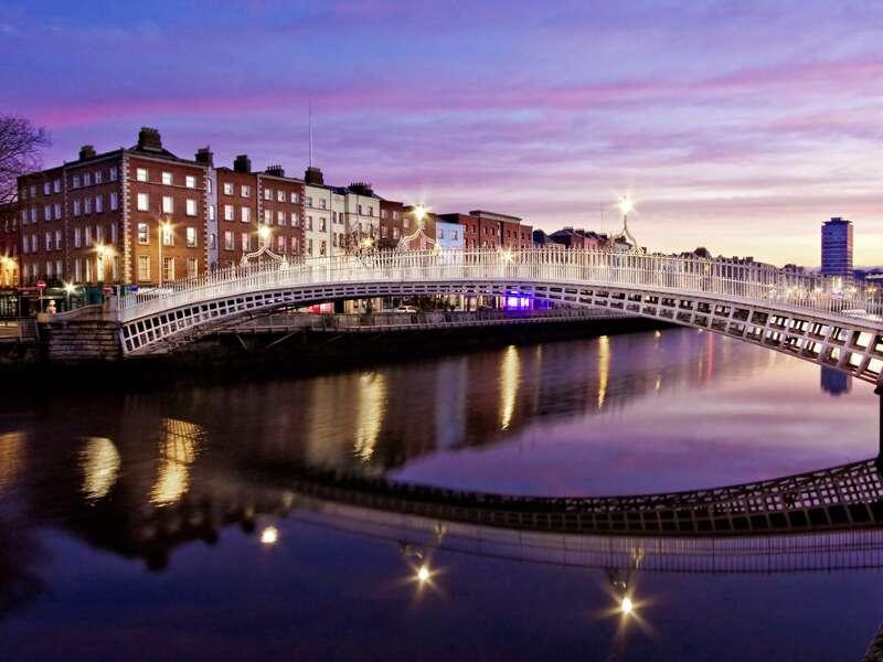 Auf unserer Studienreise durch Irland schlendern wir in Dublin über die Half Penny Bridge von einem Ufer der Liffey zum anderen. Die berühmte Bogenbrücke spannt sich im sanften Bogen über den Fluss.